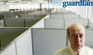 Older man sat in office with screens