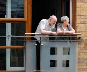older people stood on flat balcony